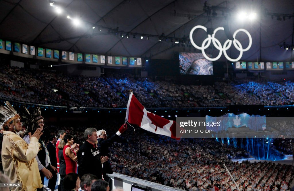 Canadian Prime Minister Stephen Harper (2nd R) looks out into the stadium as Gordon Campbell (R), the Premier of British Columbia, waves a Canadian flag during the closing ceremony of the Vancouver 2010 Winter Olympics, February 28, 2010. AFP PHOTO POOL / JIM YOUNG