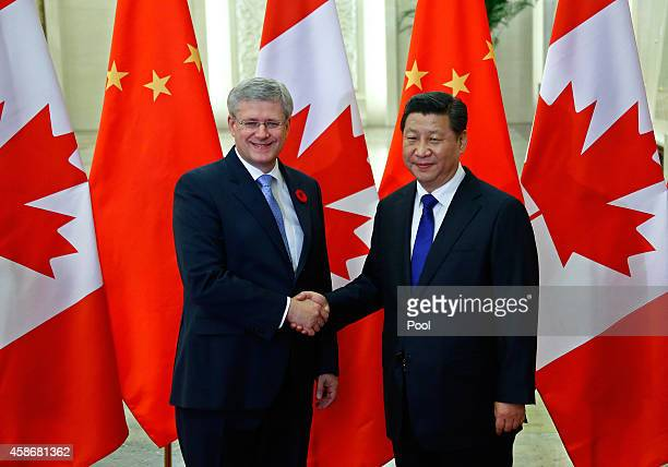 Canadian Prime Minister Stephen Harper shakes hands with Chinese President Xi Jinping during an APAC Bilateral Meeting at the Great Hall of the...