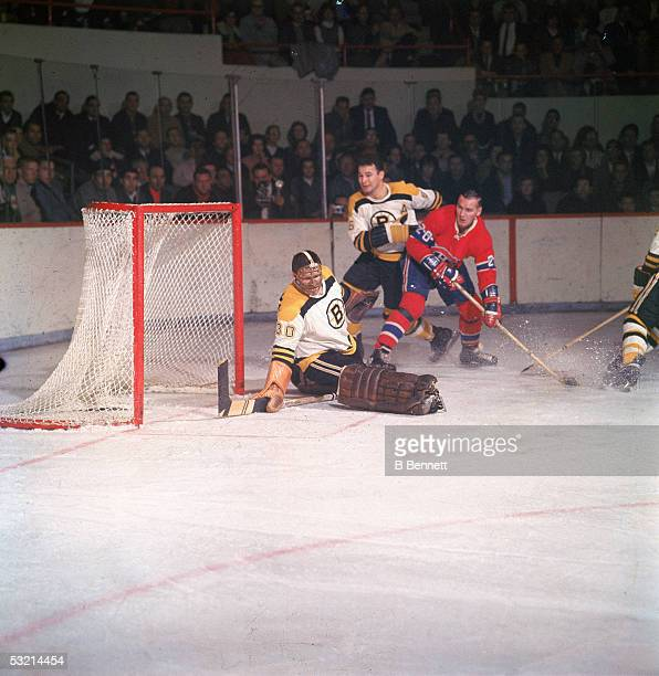 Canadian pro hockey player Bernie Parent goalie for the Boston Bruins appears to make a kick save as Montreal Canadiens forward Dave Balon moves in...