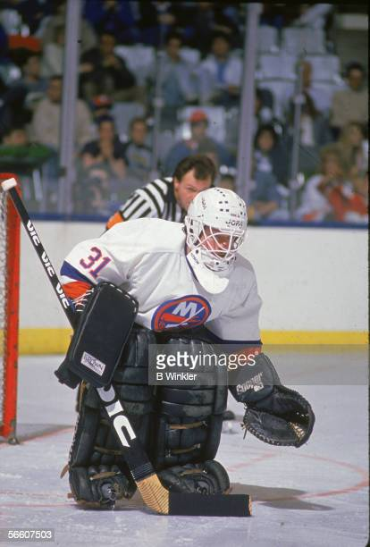 Canadian pro hockey player Billy Smith goalie for the New York Islanders guards the net during a home game Uniondale New York 1980s