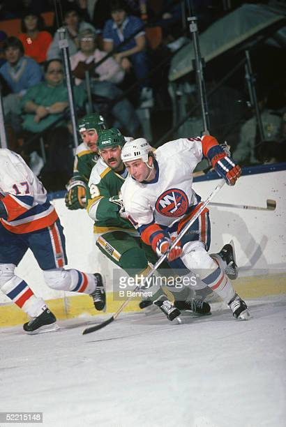 Canadian pro hockey player Brent Sutter forward for the New York Islanders skates away from Minnesota North Stars forward Dennis Maruk during a game...