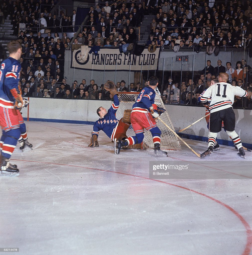 Canadian pro hockey player Ed Giacomin goalie for the New York Rangers takes a swipe at the puck as it sails over the crossbar and Ranger defenseman...