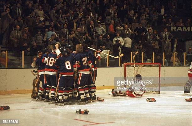Canadian pro hockey player JP Parise of the New York Islanders is mobbed by his teammates after his overtime goal helped them beat their rivals the...