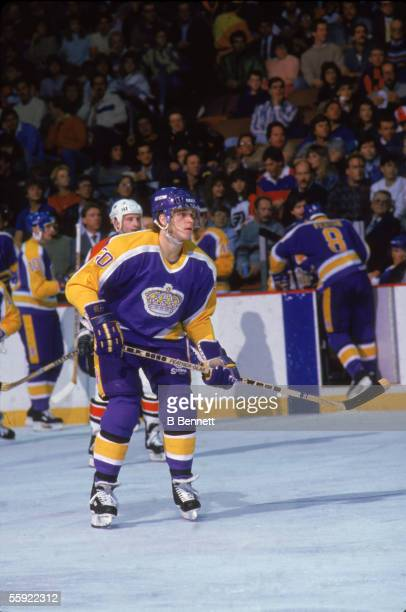 Canadian pro hockey player Luc Robitaille of the Los Angeles Kings waits for action near the bench during an away game 1980s