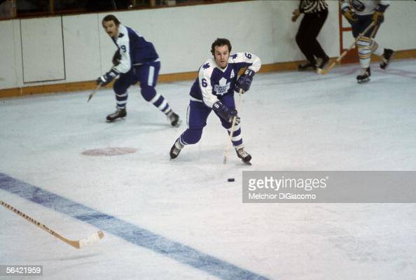 Canadian pro hockey player Ron Ellis of the Toronto Maple Leafs controls the puck as teammate Norm Ullman skates behind him during a game against the...