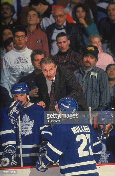 Canadian professional hockey coach Tom Watt head coach for the Toronto Maple Leafs confers with his players from the bench during a game December 1991