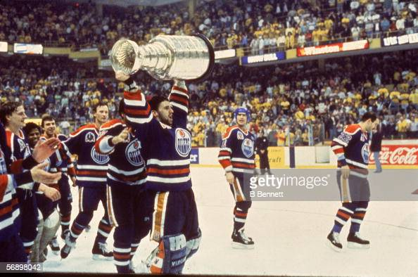 Canadian professional hockey player Bill Ranford of the Edmonton Oilers hoists the Stanley Cup over his head as he celebrates their championship...
