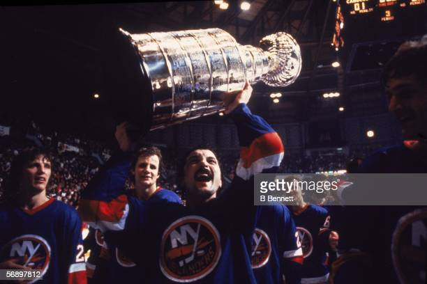 Canadian professional hockey player Bryan Trottier of the New York Islanders hoists the Stanley Cup over his head as he celebrates their championship...