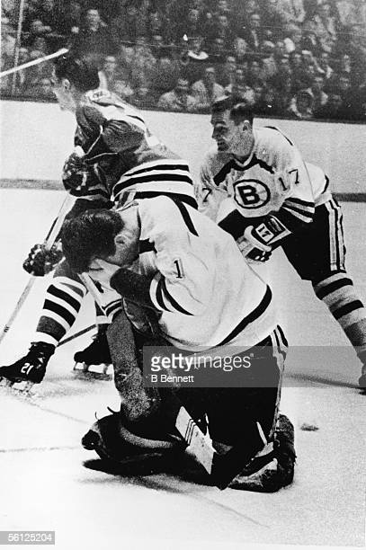 Canadian professional hockey player Ed Johnston goalie for the Boston Bruins kneels in pain with his hand on his face as Stan Mikita of the Chicago...