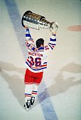 Canadian professional hockey player Glenn Anderson of the New York Rangers hoists the Stanley Cup over his head as he celebrates their championship...