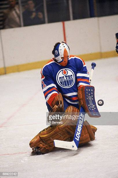 Canadian professional hockey player Grant Fuhr goalie for the Edmonton Oilers goes down on the ice to block a shot during an away game November 1981