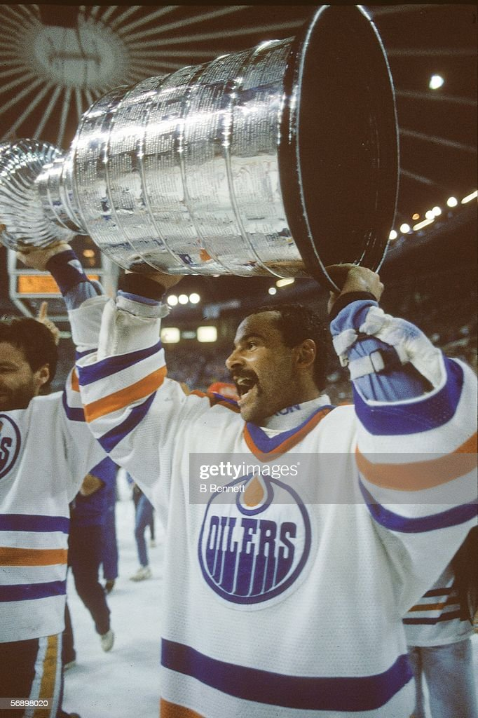 Canadian professional hockey player Grant Fuhr of the Edmonton Oilers hoists the Stanley Cup over his head as he celebrates their championship...