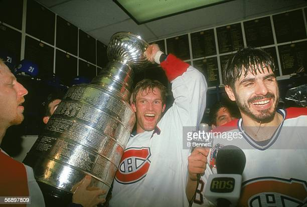 Canadian professional hockey player Kirk Muller of the Montreal Canadiens hoists the Stanley Cup over his head as he celebrates their championship...