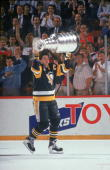 Canadian professional hockey player Mario Lemieux forward for the Pittsburgh Penguins hoists the Stanley Cup over his head and takes it for a victory...