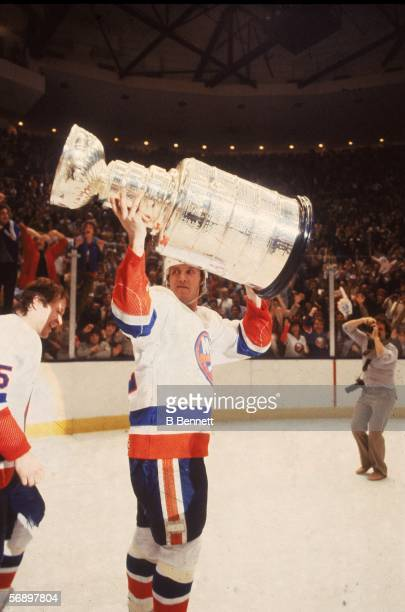 Canadian professional hockey player Mike Bossy of the New York Islanders hoists the Stanley Cup over his head as he celebrates their championship...