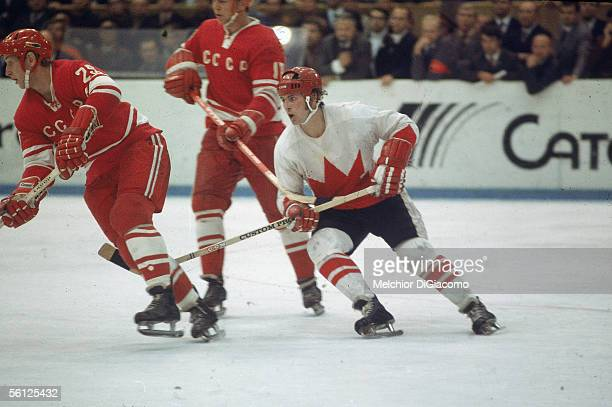 Canadian professional hockey player Paul Henderson left wing for Team Canada skates by two players from the Soviet team during a game from the Summit...