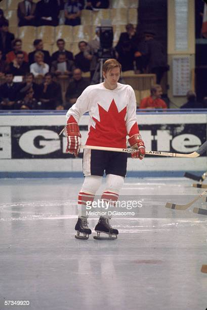Canadian professional hockey player Red Berenson of Team Canada skates past the team lineup during a game at the 1972 Summit Series against the...