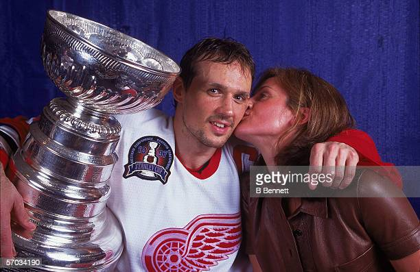 Canadian professional hockey player Steve Yzerman center for the Detroit Red Wings gets a kiss on the cheek from his wife Lisa as he poses with the...