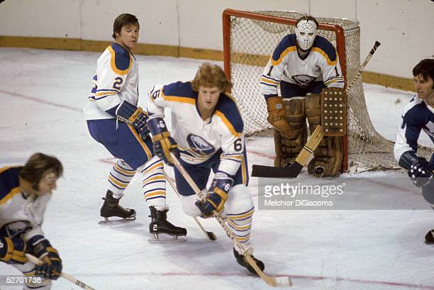 Canadian professional hockey player Tim Horton of the Buffalo Sabres skates in front of goalie Roger Crozier as teammate Jim Schoenfeld defends...
