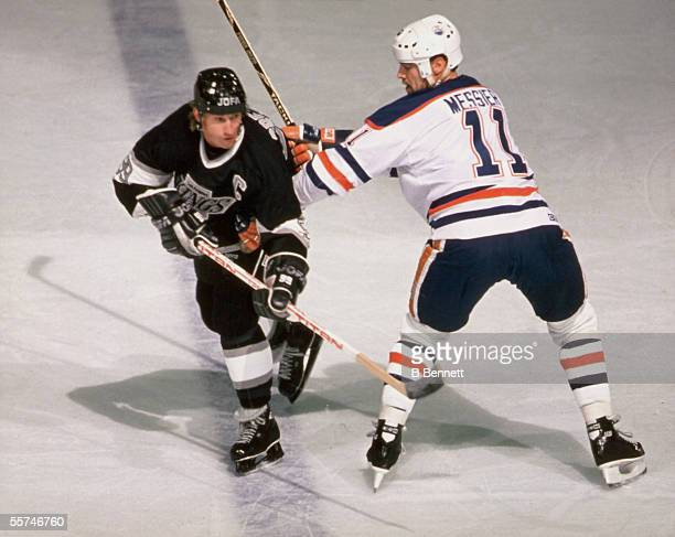 Canadian professional hockey player Wayne Gretzky center for the Los Angeles Kings is checked by Canadian professional hockey player Mark Messier...
