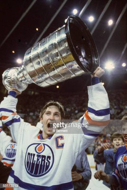 Canadian professional hockey player Wayne Gretzky of the Edmonton Oilers holds the Stanley Cup aloft as he skates a victory lap around the Northlands...