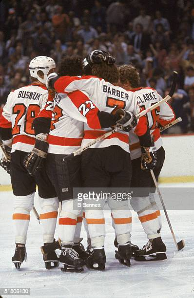 Canadian professional hockey players Mike Busniuk Reggie Leach Billy Barber and Bobby Clarke of the Philadelphia Flyers celebrate on the ice during...