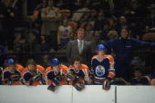 Canadian professional ice hockey coach and former player Glen Sather of the Edmonton Oilers watches the action on the ice from the bench along with...