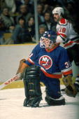 Canadian professional ice hockey player Billy Smith of the New York Islanders kneels on the ice during a road game March 1985 Smith played for the...