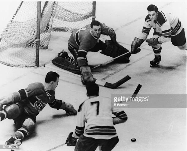 Canadian professional ice hockey player Jacques Plante goalie of the Montreal Canadiens and teammate Butch Bouchard combine forces to prevent a goal...