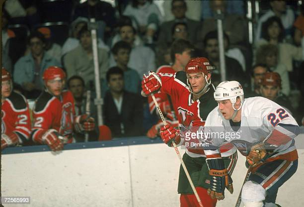 Canadian professional ice hockey player Kirk Muller of the New Jersey Devils checks Mike Bossy of the New York islanders on the ice during a game...