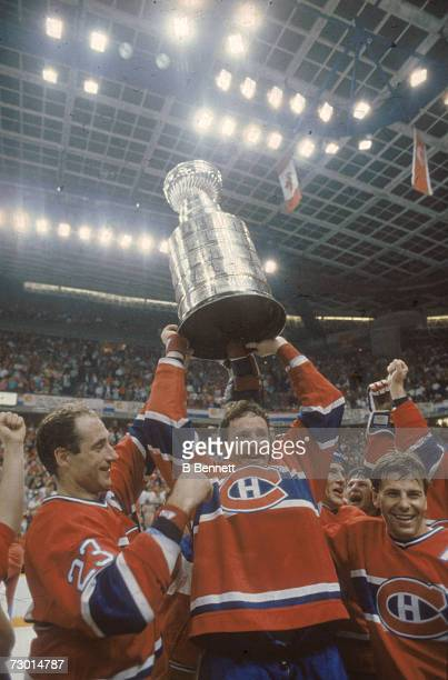 Canadian professional ice hockey players Bob Gainey and Larry Robinson of the Montreal Canadiens and Swedish teammate Mats Naslund lift the Stanley...