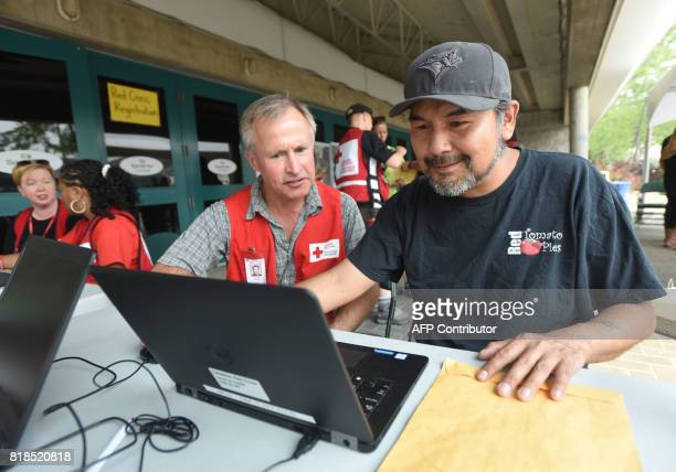 Canadian Red Cross volunteer Nicholas Albright assists Frank David with registering for help in Kamloops British Columbia on July 18 after he was...