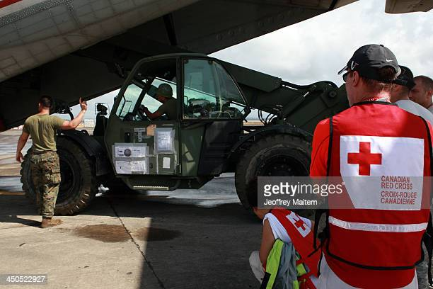 Canadian Red Cross workers oversee the unloading of their equipment from a cargo plane at the airport on November 19 2013 in Tacloban Leyte...