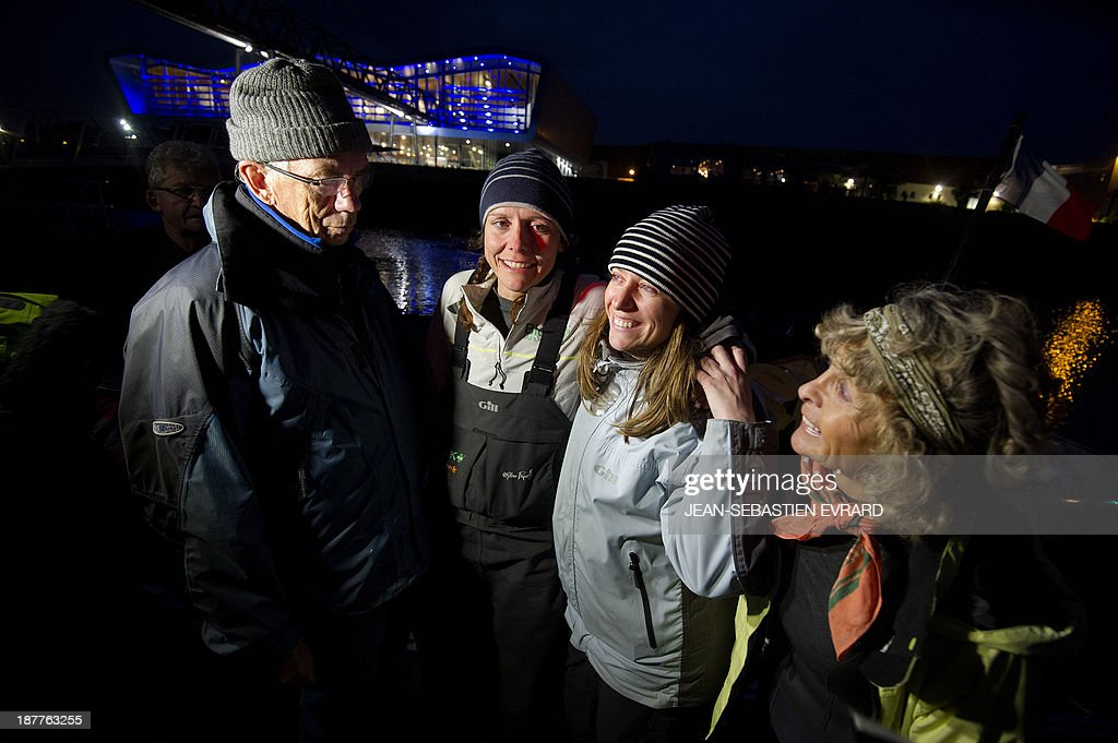 Canadian sailor Mylene Paquette (2ndL) celebrates with (LtoR) her father Jean, her sister Evelyne and her mother Gocelyne as she arrives at the Lorient harbour, western France, on November 12, 2013. Mylene Paquette, a 35-year-old from Quebec, is the first North American to have crossed the Atlantic Ocean, a 2,700 nautical mile (4,300-km) long journey, on a rowboat in 129 days between Halifax and Lorient. Ten people have so far crossed the Atlantic from west to east on a rowboat, including two French female sailors. At background, the French late yachtsman Eric Tabarly's Cite de la Voile (sailing city).