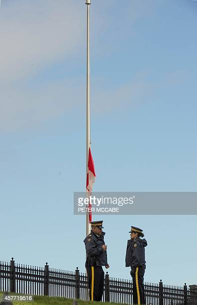 Canadian security forces guard Parliament as the national flag flies at halfmast on October 23 in Ottawa one day after multiple shootings in the...