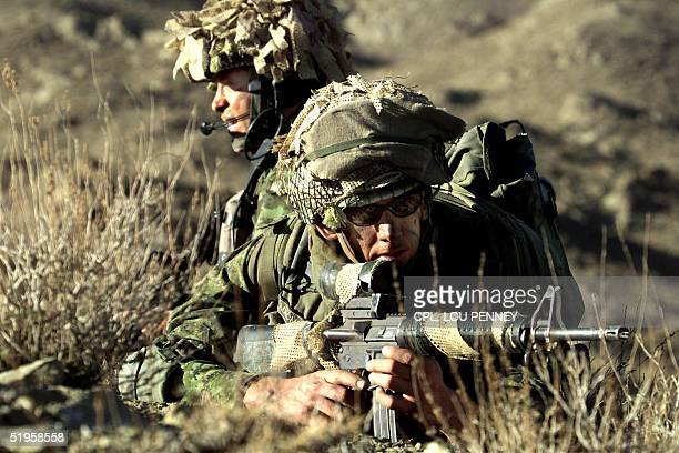 Canadian soldiers Cpl Ryan MacMillan rear and Cpl Chris Alden wait for word to move in the ShaheKot valley of Afghanistan Friday March 15 2002 The...