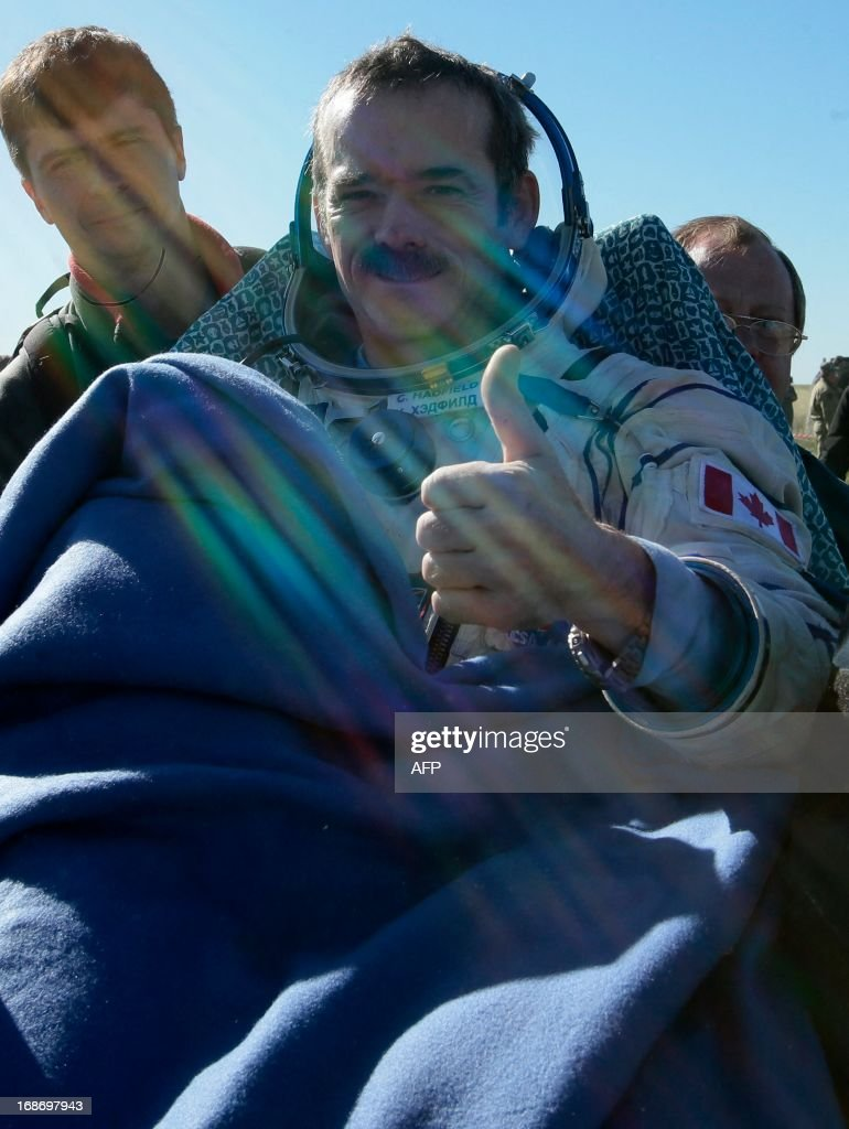 Canadian spaceman Chris Hadfield gives a thumb as Russian space agency, Roskosmos, ground personnel carry him shortly after the landing aboard the Russian Soyuz space capsule some 150 km (90 miles) southeast of the town of Zhezkazgan in central Kazakhstan on May 14, 2013. US astronaut Tom Marshburn, Canadian spaceman Chris Hadfield and Russian cosmonaut Roman Romanenko returned today to Earth aboard a Russian Soyuz-TMA capsule after a half-year mission to the International Space Station, Moscow mission control said.
