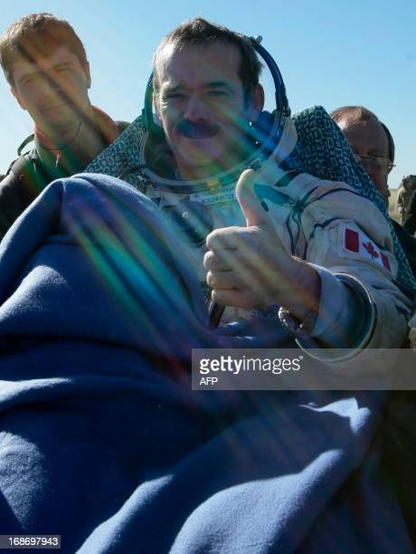 Canadian spaceman Chris Hadfield gives a thumb as Russian space agency Roskosmos ground personnel carry him shortly after the landing aboard the...