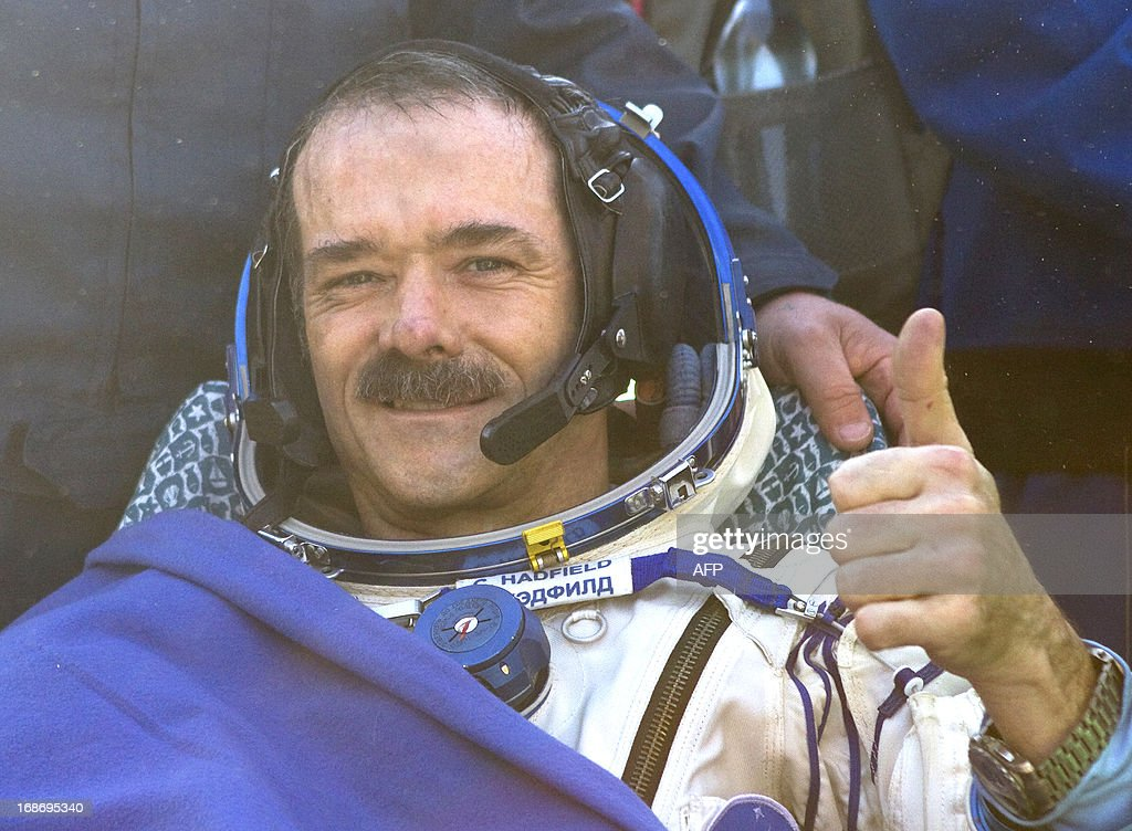 Canadian spaceman Chris Hadfield gives a thumb shortly after his landing aboard the Russian Soyuz space capsule some 150 km (90 miles) southeast of the town of Zhezkazgan in central Kazakhstan on May 14, 2013. US astronaut Tom Marshburn, Canadian spaceman Chris Hadfield and Russian cosmonaut Roman Romanenko returned today to Earth aboard a Russian Soyuz-TMA capsule after a half-year mission to the International Space Station, Moscow mission control said. AFP PHOTO / POOL / SERGEI REMEZOV