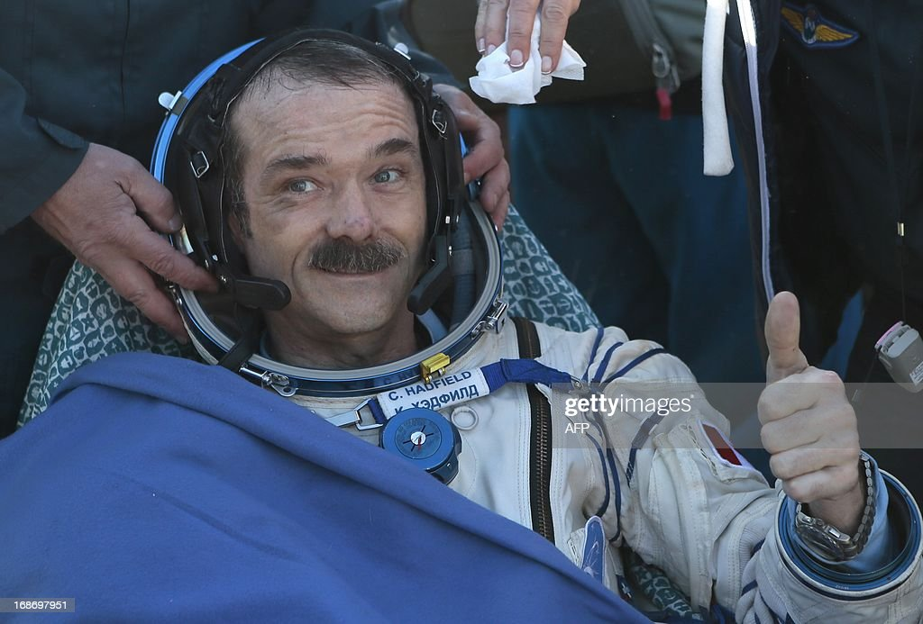 Canadian spaceman Chris Hadfield gives a thumb up shortly after the landing aboard the Russian Soyuz space capsule some 150 km (90 miles) southeast of the town of Zhezkazgan in central Kazakhstan on May 14, 2013. US astronaut Tom Marshburn, Canadian spaceman Chris Hadfield and Russian cosmonaut Roman Romanenko returned today to Earth aboard a Russian Soyuz-TMA capsule after a half-year mission to the International Space Station, Moscow mission control said.