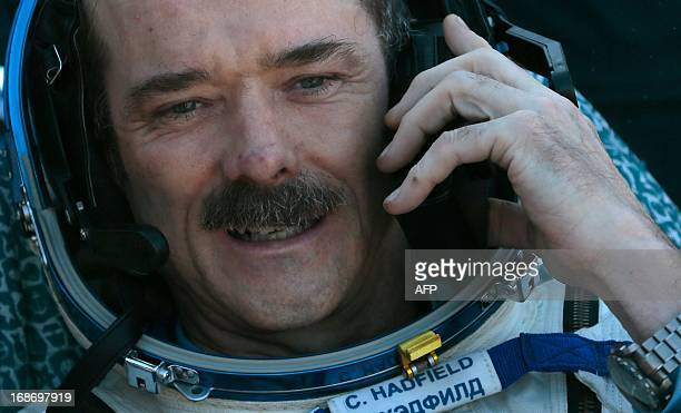 Canadian spaceman Chris Hadfield speaks on the phone shortly after the landing aboard the Russian Soyuz space capsule some 150 km southeast of the...