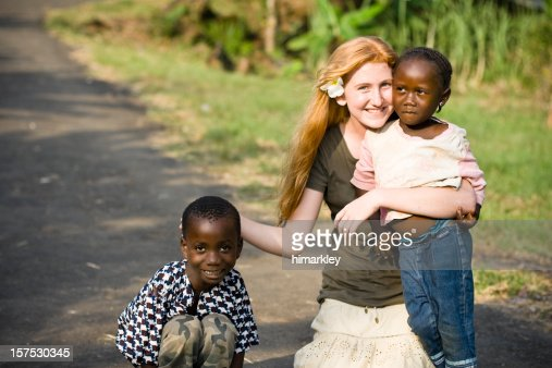 Canadian teen holding two needy African children