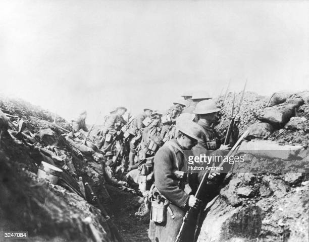 Canadian troops in a trench prepare their rifles with bayonets before going 'over the top' Western Front Somme France World War I