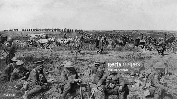 Canadian troops sit and take a break in a field during a pause in their attack on the Cambrai front France Western Front World War I In the midground...