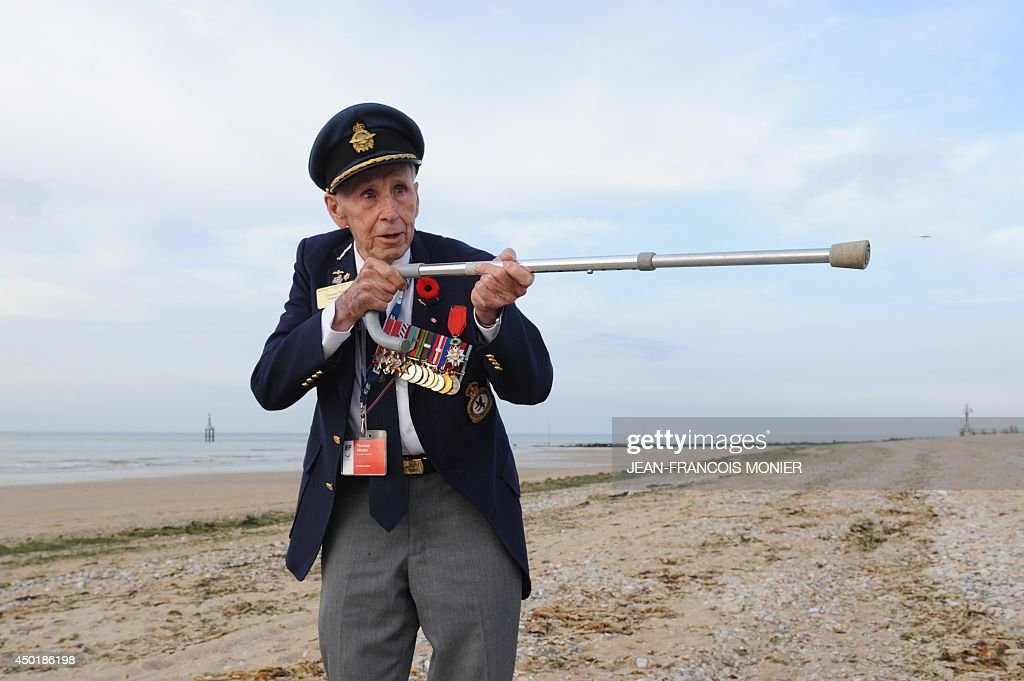 A Canadian World War II veteran mimics hold a rifle with a crutch after a bi-national France-Canada ceremony on Juno Beach, in Courseulles-sur-Mer, Normandy, on June 6, 2014, as part of the events marking the 70th anniversary of the World War II Allied landings in Normandy.