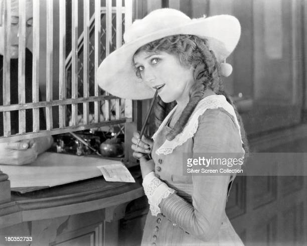 CanadianAmerican actress Mary Pickford at a bank counter in a promotional still circa 1920