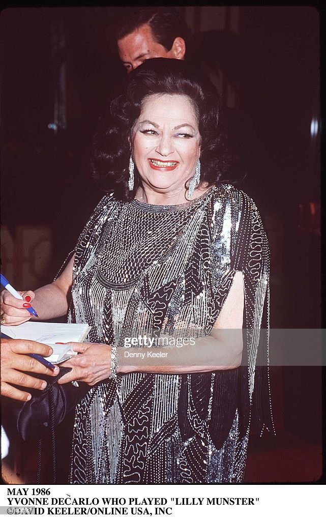 Canadian-born actress Yvonne de Carlo wears a silver metal dress as she smiles and signs an autograph, May 1986.