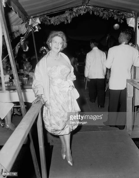 Canadianborn beautician and cosmetics entrepreneur Elizabeth Arden dressed in a ruched evening gown leans against a railing underneath a covered...