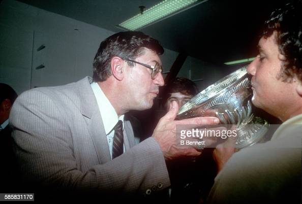 Canadianborn hockey coach and former professional hockey player Al Arbour head coach of the New York Islanders drinks champagne out of the Stanley...