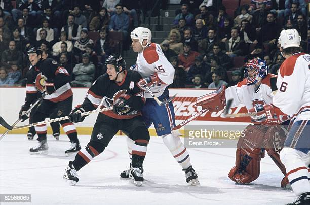 Canadiens defenceman Jassen Cullimore tries to contain Senators forward Daniel Alfredsson in front of goaltender Jocelyn Thibault in a game at the...